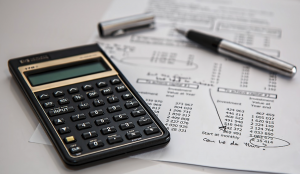 Calculator and paperwork showing retirement investment accounts.